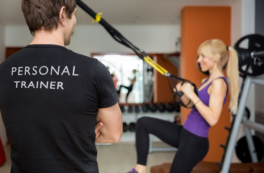 26754107 - personal trainer, with his back facing the camera, looking at his client